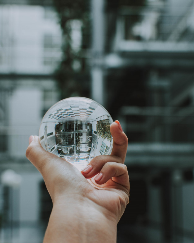 person-holding-clear-crystal-glass-ball-with-reflection-building_181624-4779